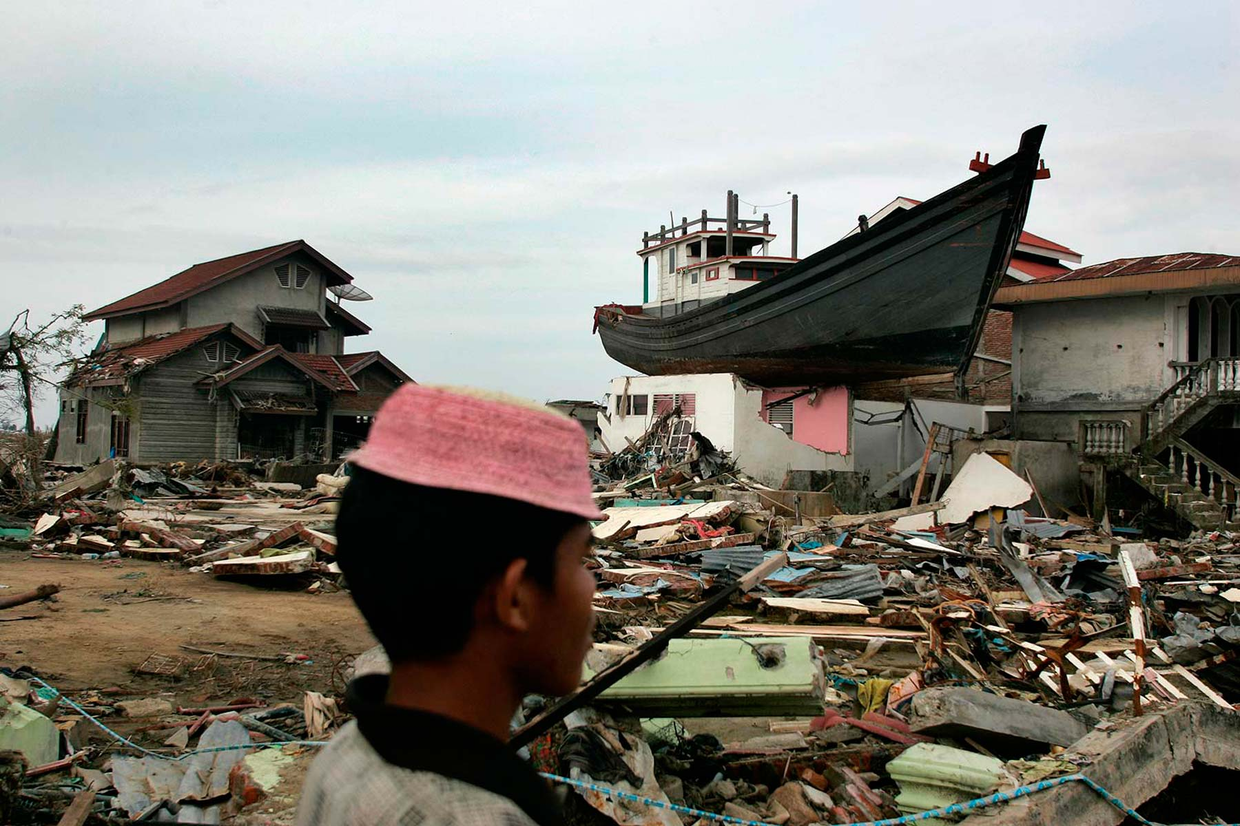 Aceh boy walks past boat on top of house after tsunami