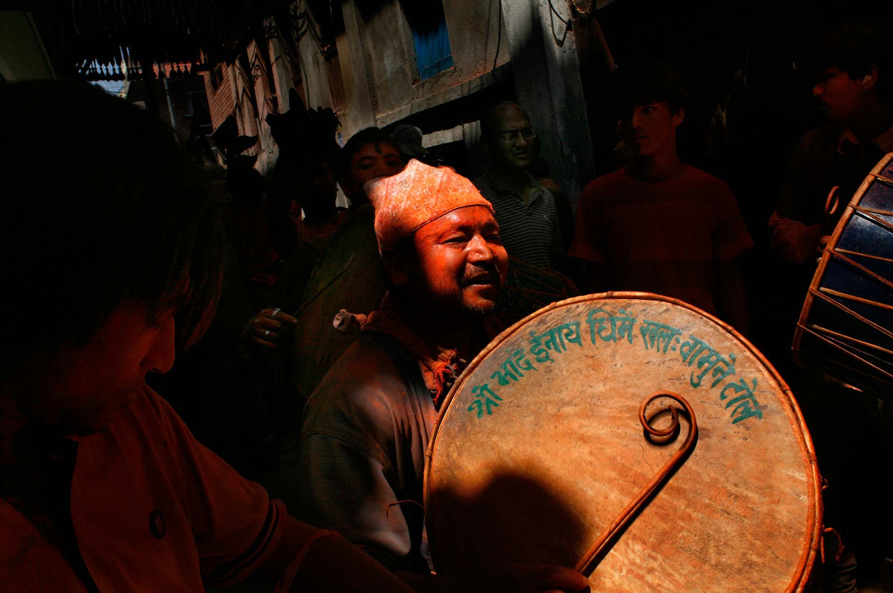Nepal man in red dye beats drum Bhaktapur