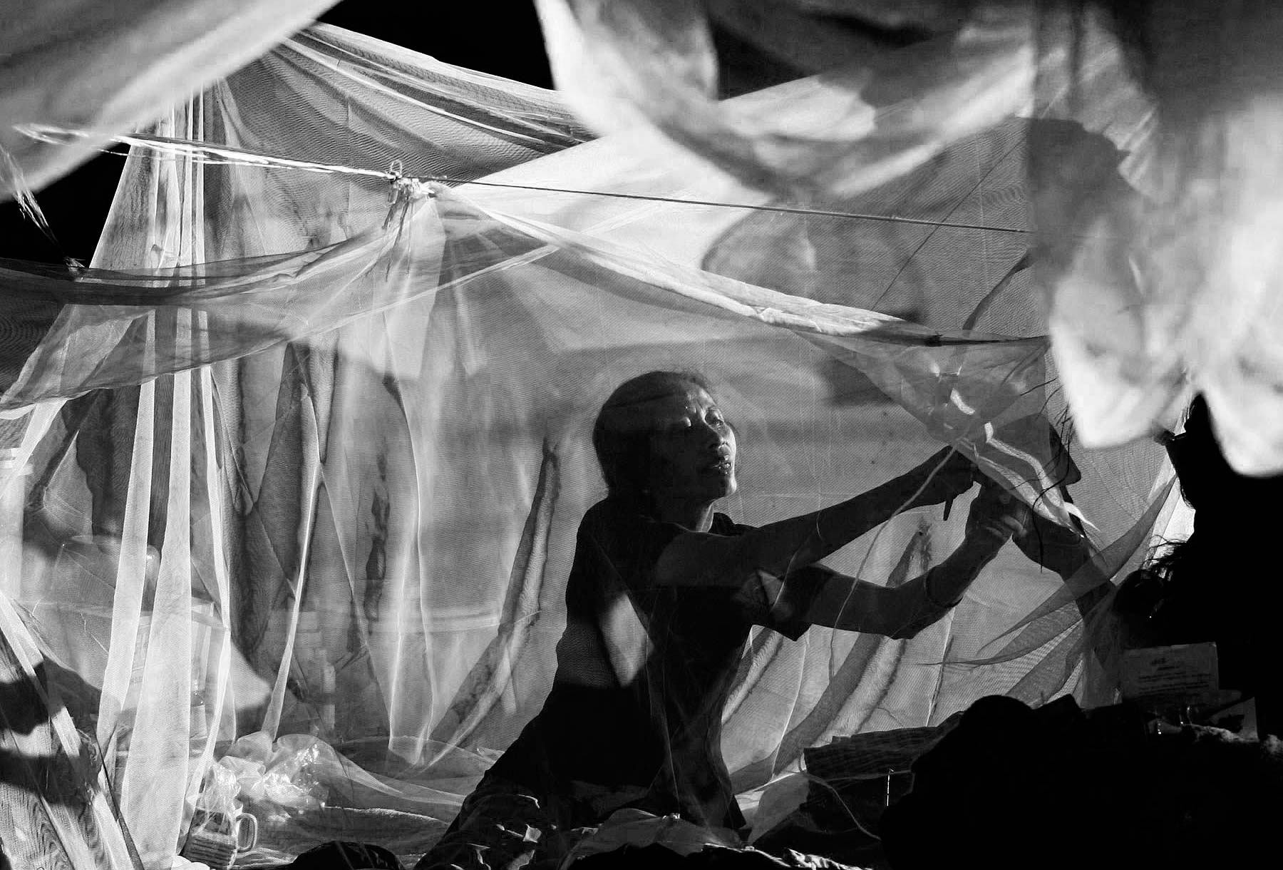East Timor woman arranges mosquito netting at Refugee camp
