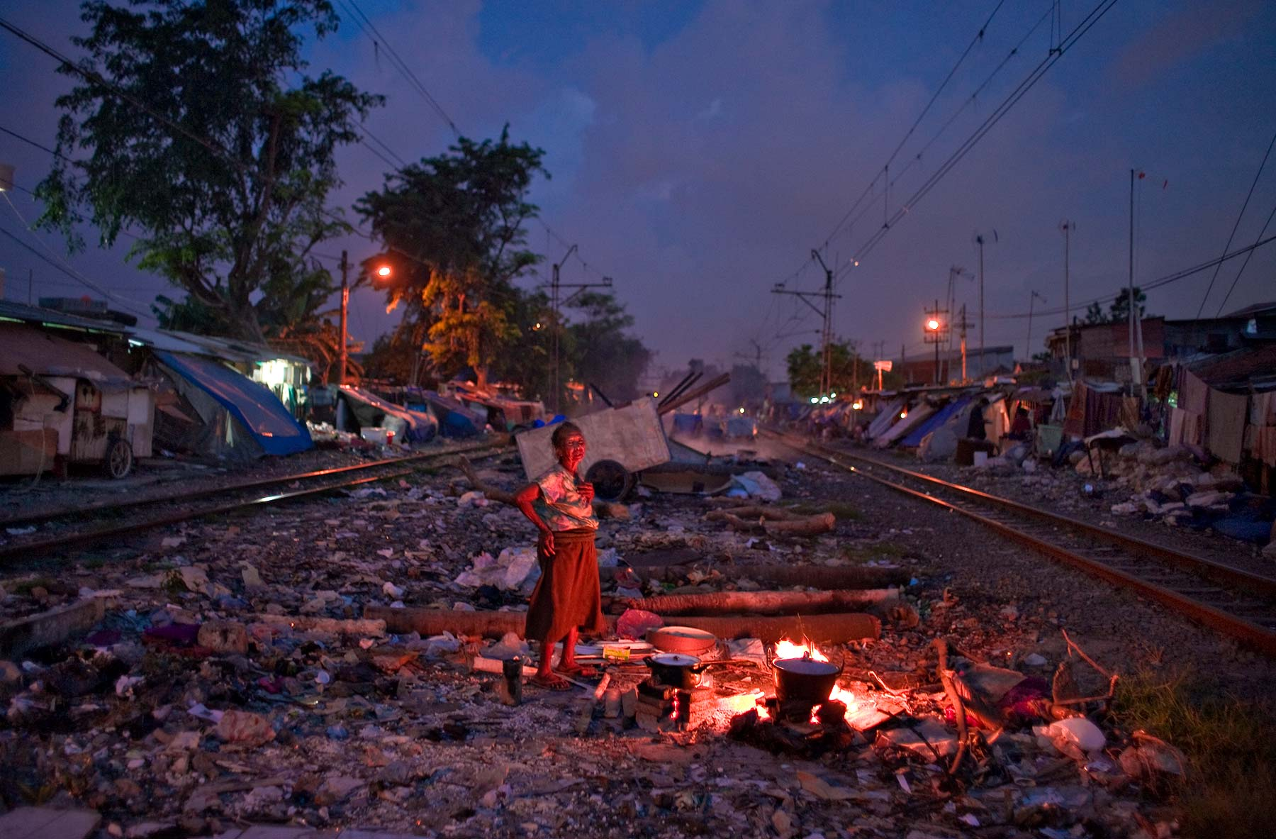 Indonesia woman cooks her dinner on railway track in East Jakarta