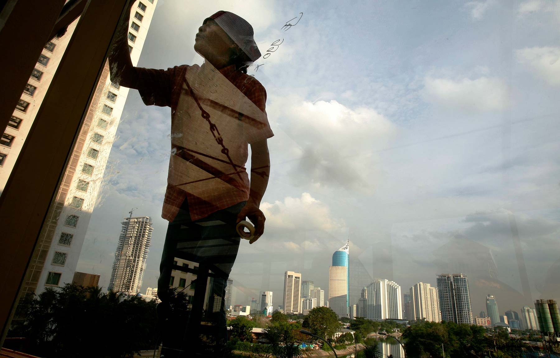Indonesian Laborer washes window skyscrapers in Jakarta Indonesia
