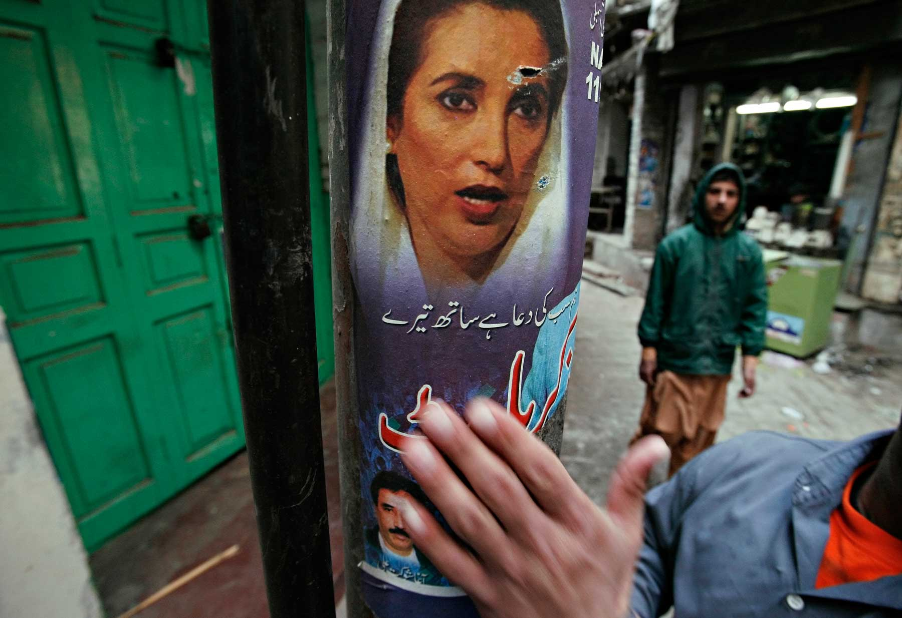 Man pats election poster for Benazir Bhutto after her assassination