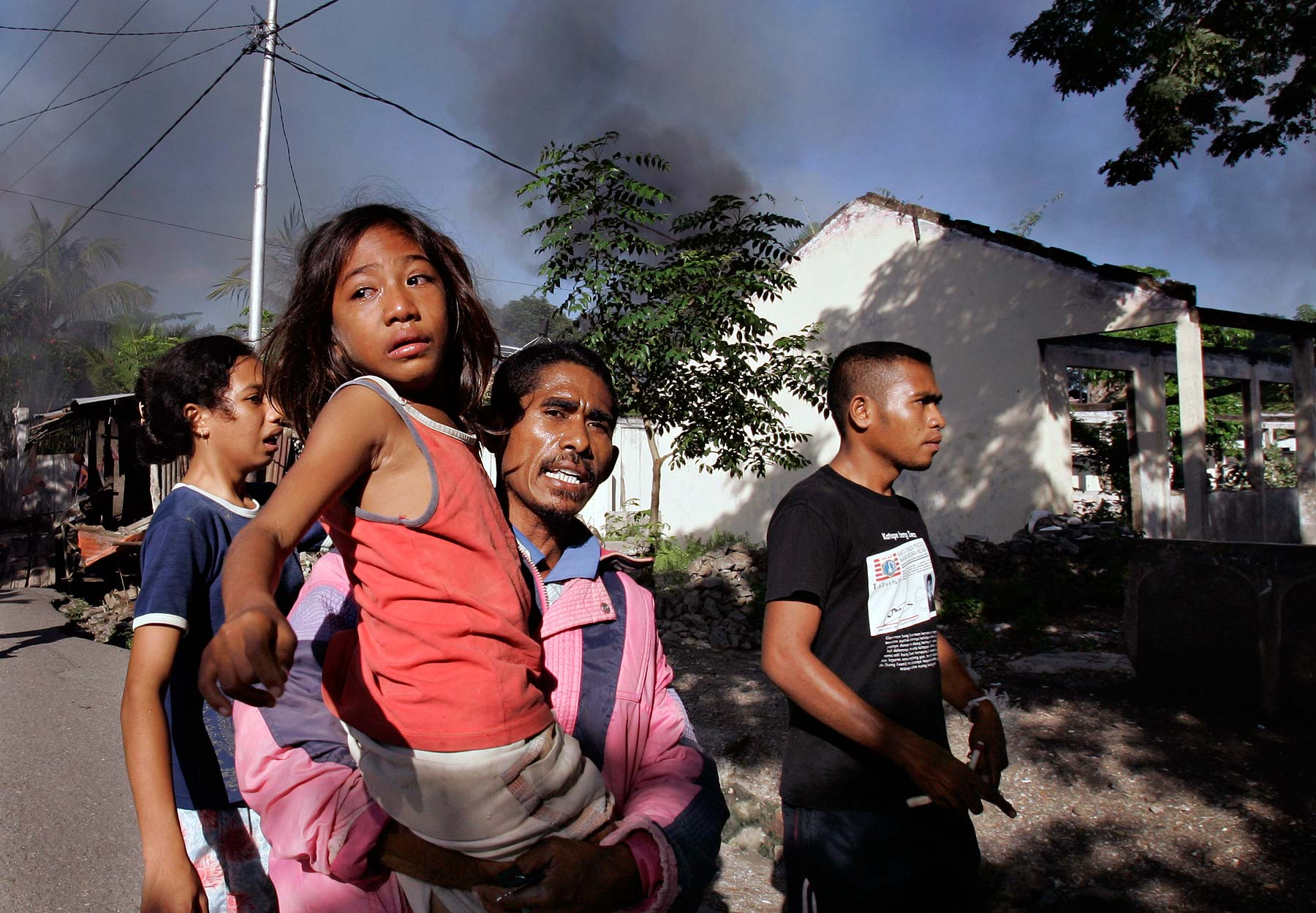 East Timor girl carried as gangs burn a neighbourhood