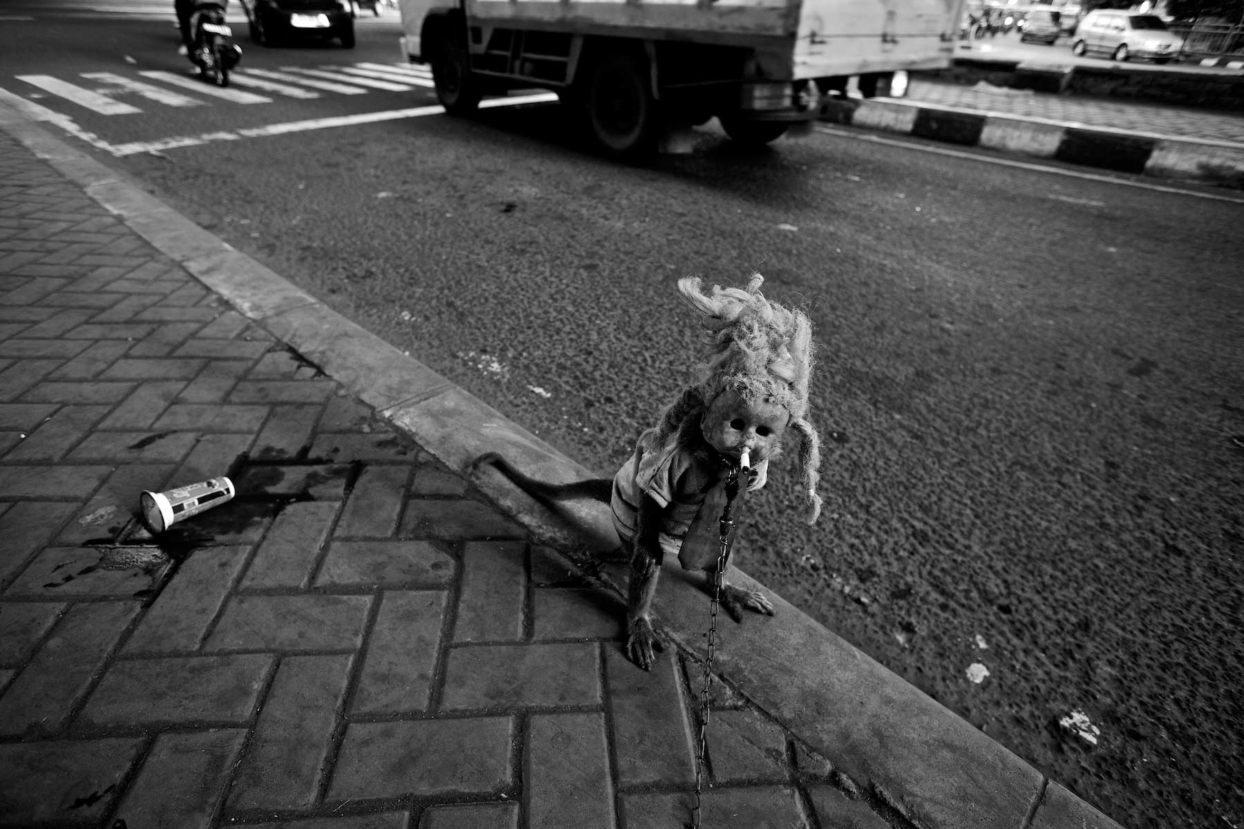 masked monkey performs on street Jakarta, Indonesia