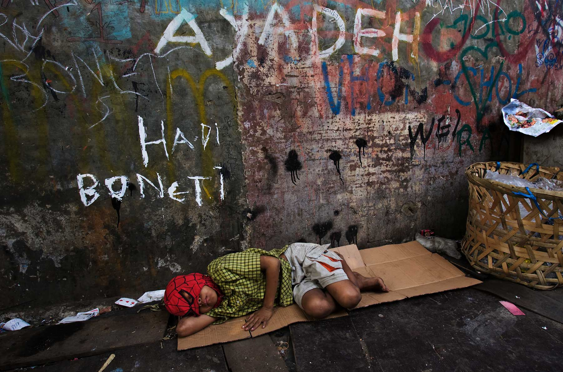 Boy sleeps with Spiderman Mask slum Jakarta Indonesia